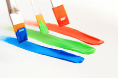 Paint brush and colors. Brush on a piece of paper draw 3 colors Stock Photo