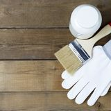 Paint, paint brush and construction gloves on a background of wooden boards, copy space, repair concept royalty free stock photos