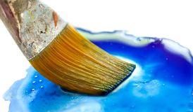 Paint brush dipping into paint. royalty free stock photos