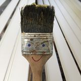 Mrs Paint Brush. Paint brush with dried linseed oil painted as a funny figure royalty free stock photo