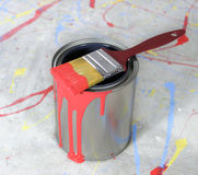 Paint Brush Dripping with Red Paint on Paint Can. Paint brush dripping with red paint sitting on a paint can against paint-spattered drop cloth Royalty Free Stock Photos