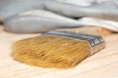 Paint brush and gloves on wooden table royalty free stock photography