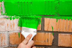 Paint brush with green color on brick wall Stock Image