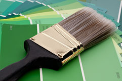 Paint brush on green paint samples Stock Images