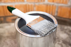 Paint brush in grey color laying on can Stock Image