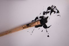 Paint brush ink blot splatter. Angled paint brush with black spattered paint that looks like ink blot Royalty Free Stock Photography