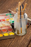 Paint brush in a jar filled with water and watercolors Stock Photos