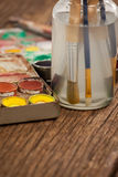 Paint brush in a jar filled with water and watercolors Royalty Free Stock Photography