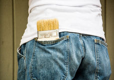 Paint brush in Jeans pocket. Man painting with spare paint brush in his back pocket stock image