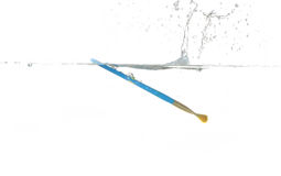 Paint brush making a splash in water Royalty Free Stock Photography