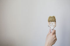 Paint brush in a man's hand on a white background .  Process concept. Stock Images