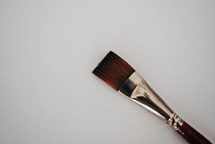 Paint brush. With maroon handle on white canvas Stock Image