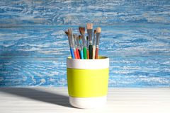 Paint brush in the mug. Paintbrush in mug in front of a rustic, blue wall in the background Royalty Free Stock Photography
