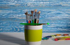 Paint brush in the mug. Paintbrush in mug in front of a rustic, blue wall in the background Stock Photos