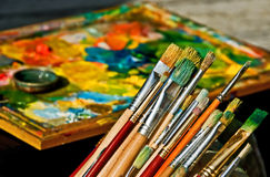 Paint brush and oil colors. A row of paint brushes and a frame with bright color mix under the sun royalty free stock photo