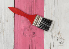 Paint brush and pink wooden board Royalty Free Stock Photo