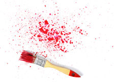 Paint brush with red gouache sprays near on white canvas in top view Royalty Free Stock Photography