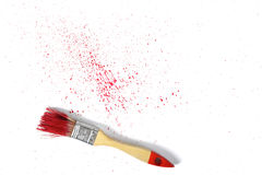 Paint brush with red gouache sprays near on white canvas in top view Royalty Free Stock Image