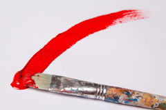 Paint brush with red paint stroke over white Royalty Free Stock Photo