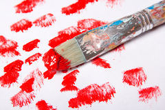 Paint brush with red paint strokes over white Stock Photos