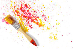 Paint brush with red and yellow gouache sprays near on white canvas in top view Stock Photography