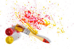 Paint brush with red and yellow gouache sprays near on white canvas in top view Stock Photos