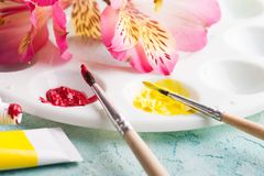 Paint brush, red, yellow watercolor paint with spring flowers Royalty Free Stock Photo