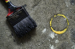 Paint brush with splatter. A paint brush with black paint and a yellow paint splash on cement Royalty Free Stock Image
