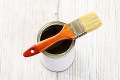Paint brush and varnish can, paintbrush and transpicuous lacquer. White color container on wooden floor background Royalty Free Stock Images