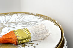 Paint brush with a wooden handle in white paint. Paint tools in the work. Repair and finishing works.  royalty free stock photography
