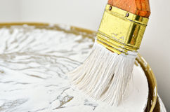 Paint brush with a wooden handle in white paint. Paint tools in the work. Repair and finishing works.  royalty free stock image