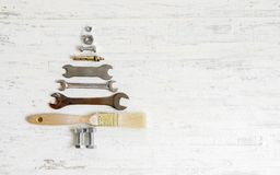 Paint brush wrench, nuts and bolts decorated as christmas tree o. N a white wooden background. Christmas greeting card and Happy new year greeting card concept royalty free stock photos