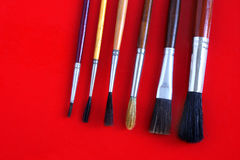 Paint brushes. Several ready to be used paintbrushes over red background Stock Photography