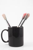 Paint brushes. In a cup on a neutral background Stock Photos