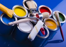 Paint and brushes. Cans with paint and brushes on the blue background royalty free stock photo