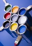 Paint and brushes. Cans with paint and brushes on the blue background Royalty Free Stock Image