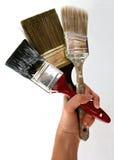Paint Brushes 3. Hand holding three paint brushes royalty free stock photos