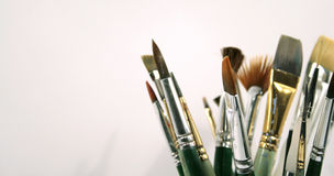 Paint brushes. Assorted used paint brushes in a glass container stock photo
