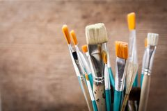 Paint brushes against wooden background stock images