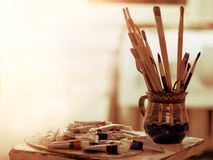 Paint brushes art pot. Easel with oil and watercolor paints. Paint brushes in art pot. Easel with oil and watercolor stack paints in morning sunlight dawn stock photography