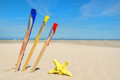 Paint brushes at beach stock image