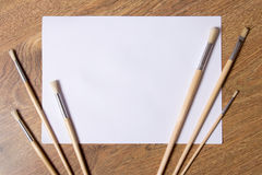 Paint brushes and blank white paper on wooden background Stock Photography