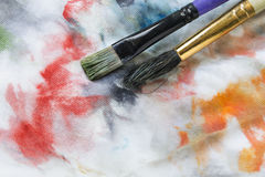 Paint brushes on canvas Stock Photography