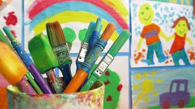 Paint Brushes In Classroom With Paintings On Wall. Tracking shot moving past paint brushes in children`s classroom with paintings on the wall stock footage