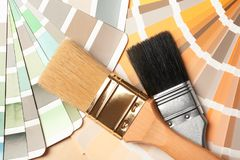 Paint brushes on color palettes. Top view stock images