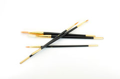 Paint brushes crossed. Brushes crossed new black with gold trim isolated on white Stock Images