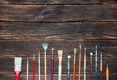 Paint brushes on a dark wooden background, top view. Concept of. Art Stock Photo