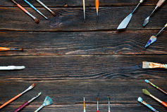 Paint brushes on a dark wooden background, top view. Concept of Stock Image
