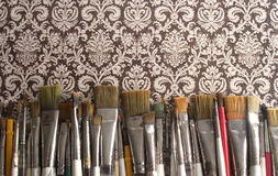 Paint Brushes on Decorative Paper. Many worn paint brushes on a decorative patterned background Royalty Free Stock Photos