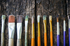 Paint brushes of different sizes have different colors in a row horizontally on an old wooden Stock Images